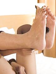 Slick and shiny Ladyboy feet caress a thick black dildo