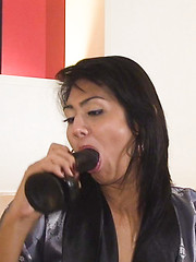 Slick and shiny Ladyboy feet caress a thick black dildo