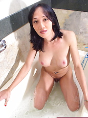 Busty she-male playing with her body while taking a foam bath