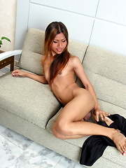 Superb Asian shemale stripping on a couch to flash her assets